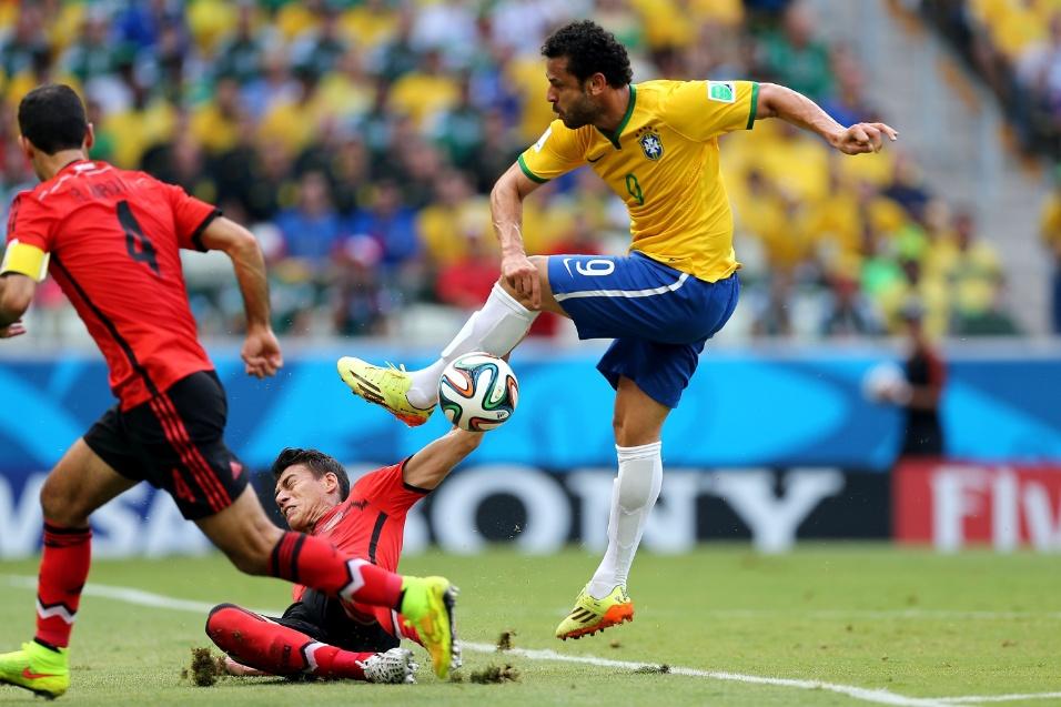17.jun.2014 - Marcado de perto por mexicano, Fred tenta a finalização na partida no Castelão
