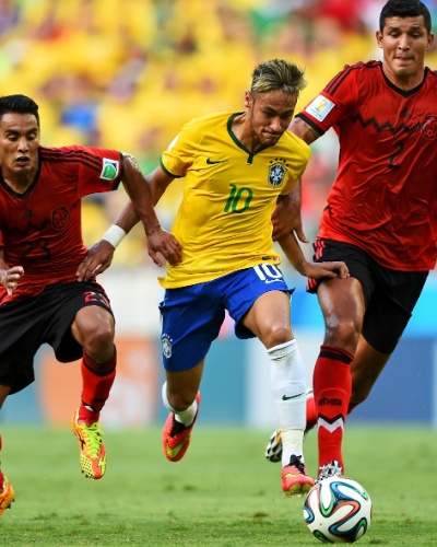 17.jun.2014 - Neymar arranca com a bola e escapa da marcação de dois mexicanos no Castelão