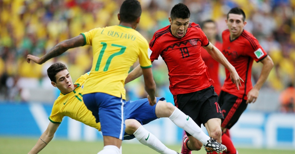 17.jun.2014 - Oscar divide a bola com Oribe Peralta, do México, no início da partida no Castelão