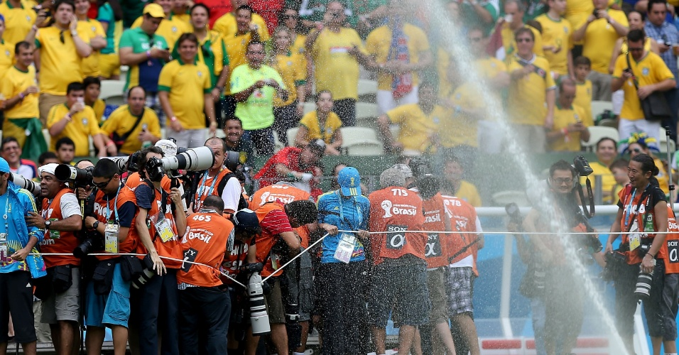 17.jun.2014 - Sistema de irrigação molha fotógrafos antes da partida entre Brasil e México, no Castelão