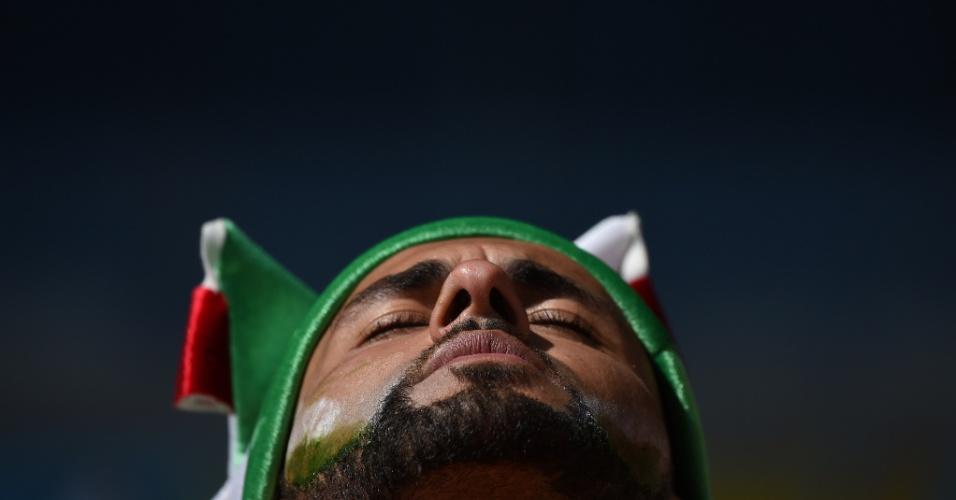 Torcedor da Argélia parece rezar embaixo de sol forte no Mineirão