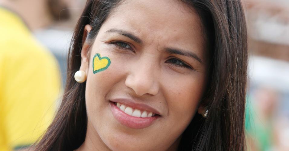 Torcedora pinta coração com as cores do Brasil para apoiar a seleção contra o México