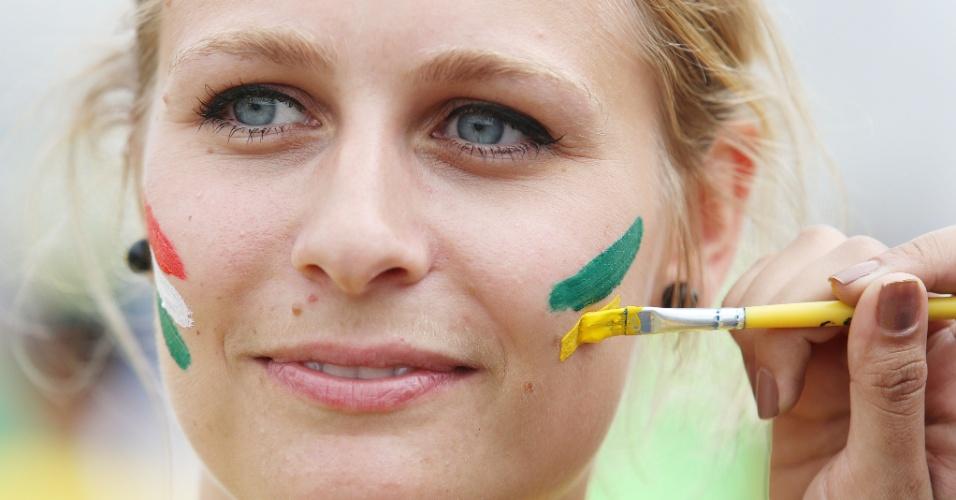 Torcedora pinta o rosto tanto com as cores brasileiras quanto com as mexicanas