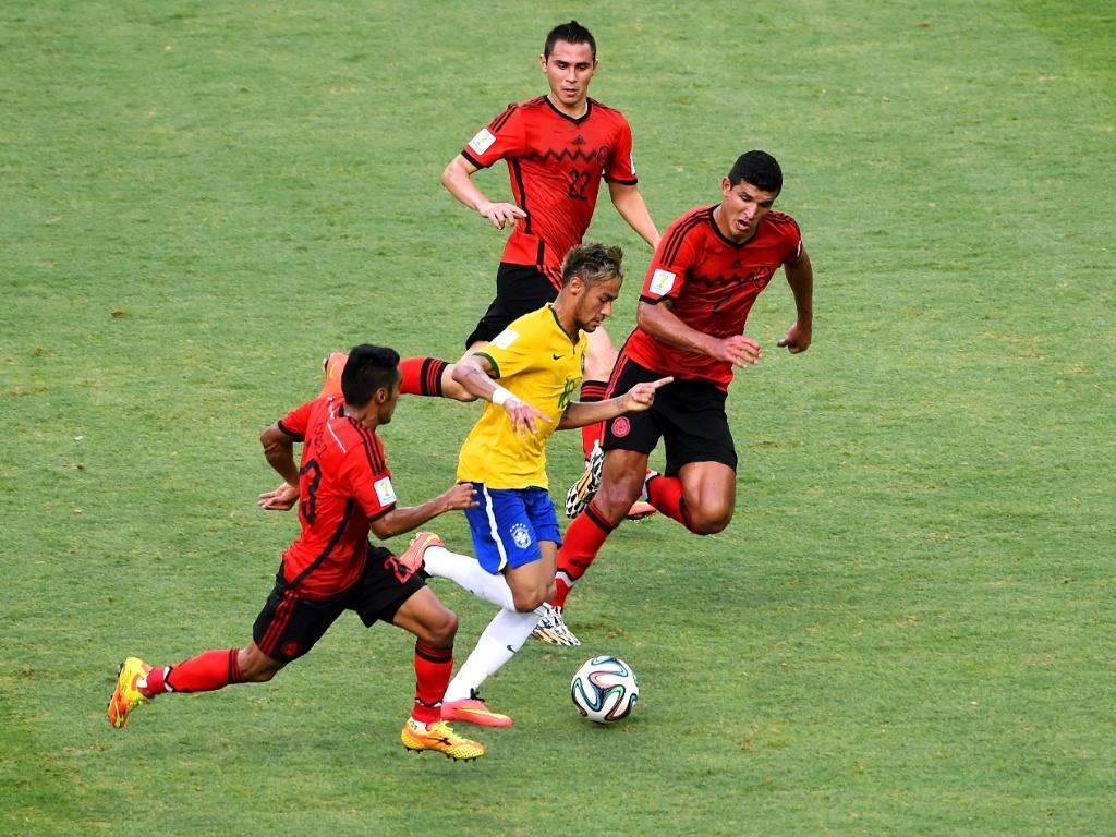 17.jun.2014 - Três mexicanos acompanham Neymar, que tenta escapar da marcação na partida no Castelão