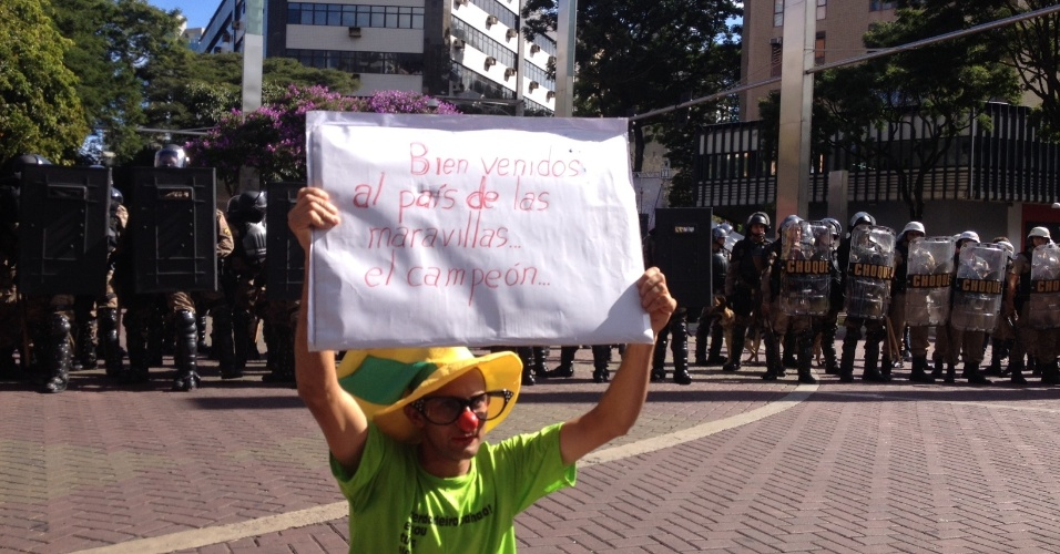 """Vestido de palhaço, manifestante exibe cartaz dizendo """"bem-vindo ao pais das maravilhas, o campeão"""""""