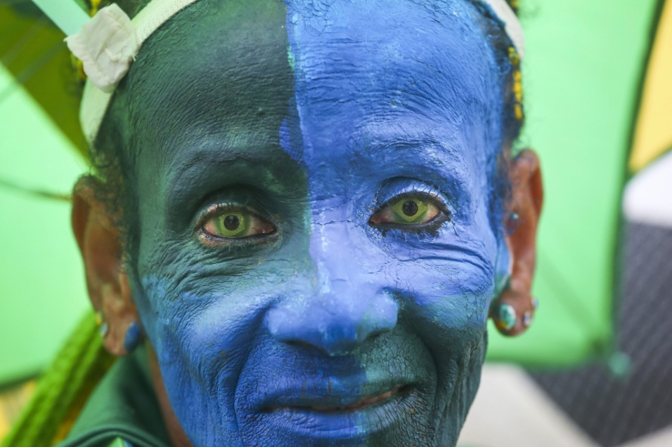 17.jun.2014 - Torcedora não se contentou apenas em pintar o rosto; ela colocou lentes de contato com o desenho da bandeira brasileira