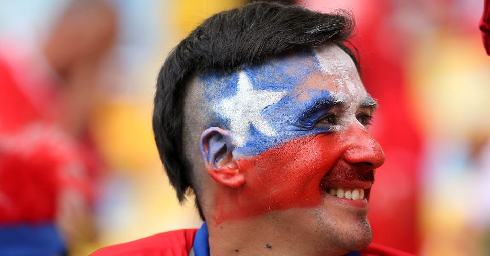 18.jun.2014 - Torcedor pinta o rosto com a bandeira do Chile no Maracanã antes da partida contra a Espanha