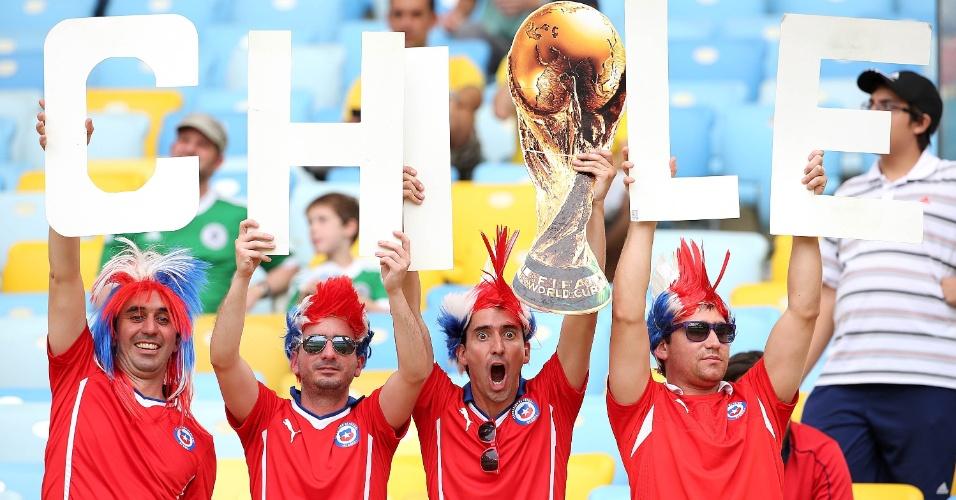18.jun.2014 - Torcedores chilenos mostram confiança na vitória e exibem a taça da Copa do Mundo no Maracanã