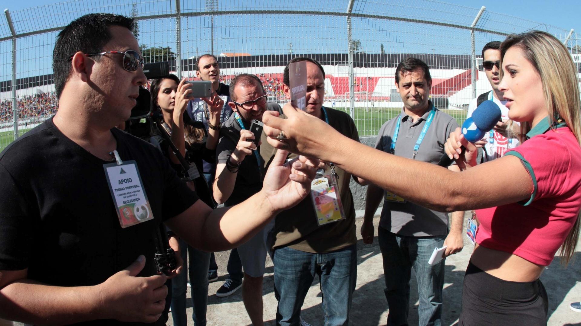 Andressa Urach mostra a credencial para os seguranças, mas de nada adianta. Apresentadora foi retirada da beira do gramado do treino aberto da seleção de Portugal, no Moises Lucarelli