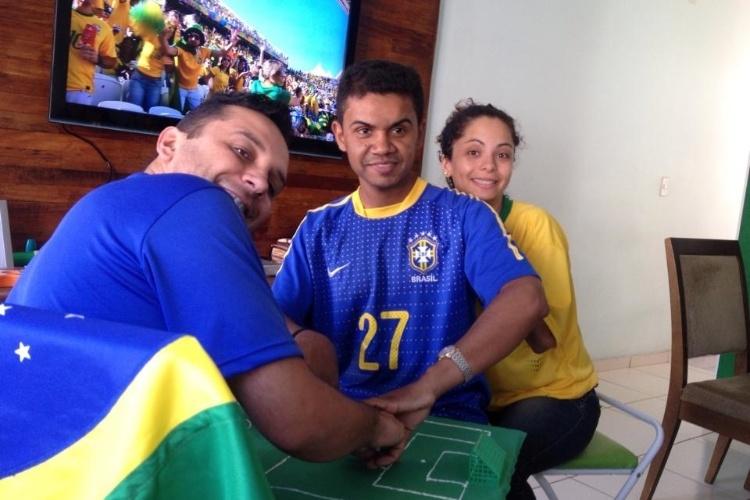 """Carlos, de 26 anos, é ajudado por Hélio e  Regiane a voltar a experimentar uma Copa. Surdocego, ele conseguiu """"enxergar"""" a estreia do Brasil na Copa por meio do tato"""