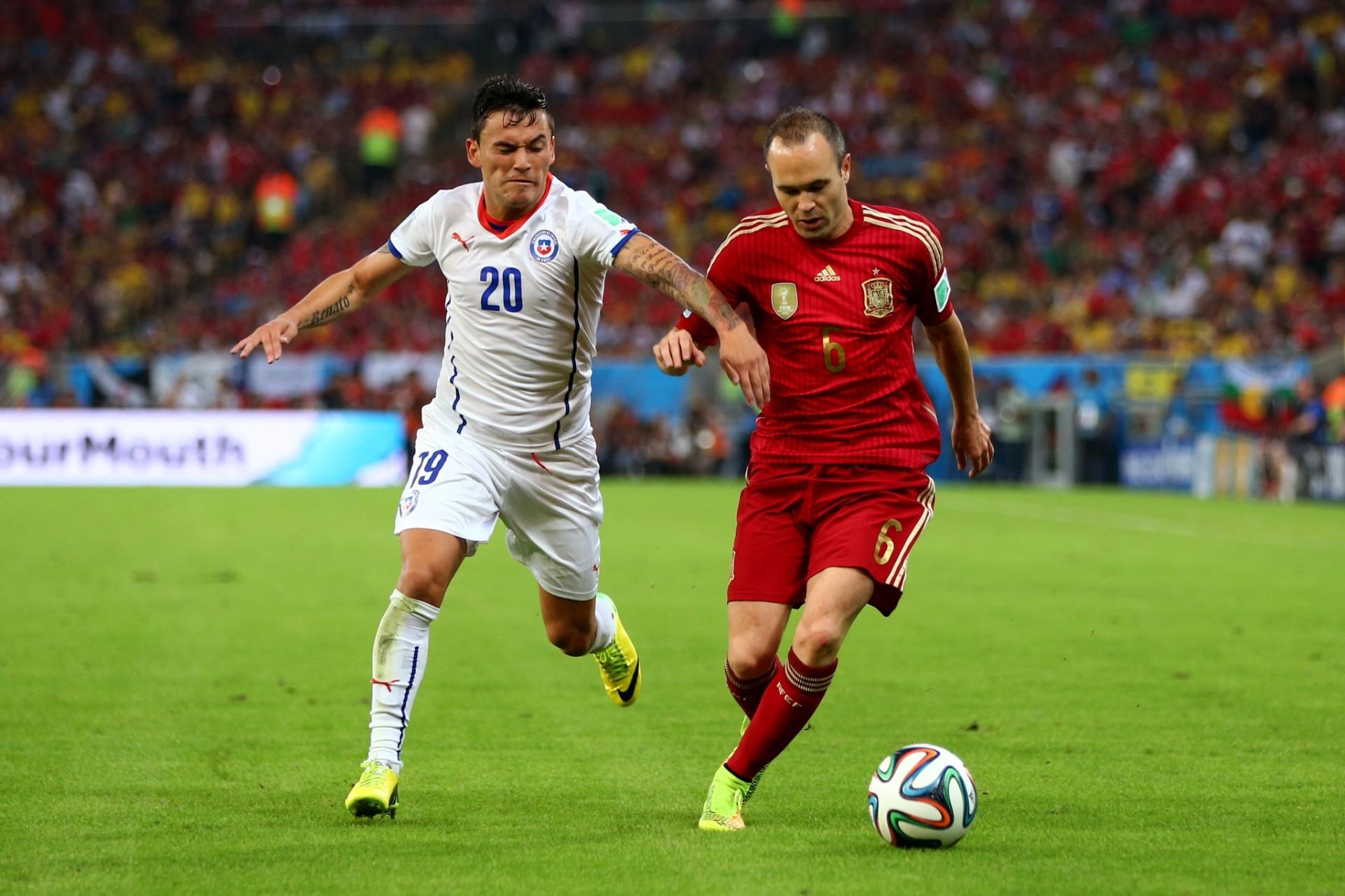 Chileno Aránguiz, que entrou em campo com o número 20 na camisa e o 19 no calção, briga pela bola com Iniesta no Maracanã