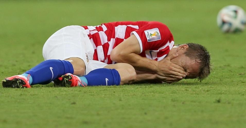Croata Luka Modric coloca a mão no rosto e fica caído no gramado após sofrer falta