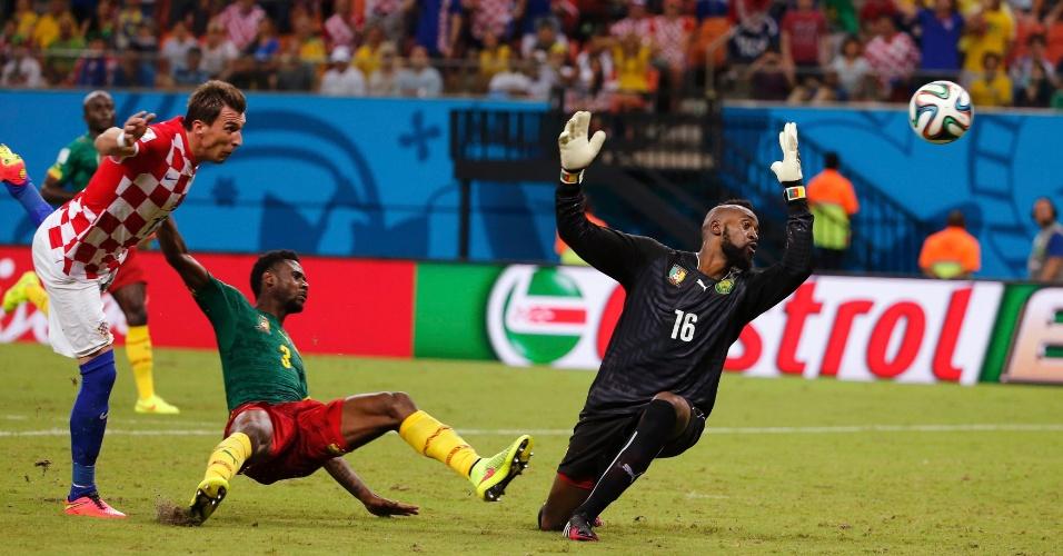 Mario Mandzukic finaliza enquanto goleiro e defensor de Camarões observam o destino da bola