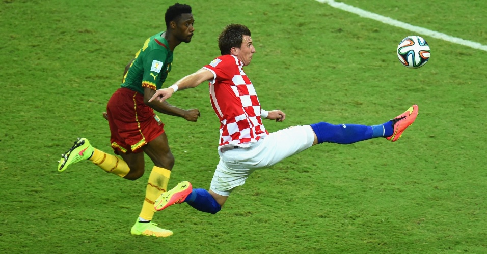 Observado pelo camaronês Nicolas N'Koulou, o atacante croata Mario Mandzukic estica a perna direita para dominar a bola