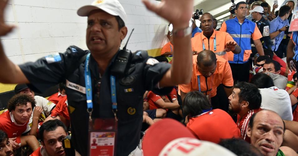 Policial gesticula enquanto torcedores chilenos permanecem detidos no centro de imprensa do Maracanã