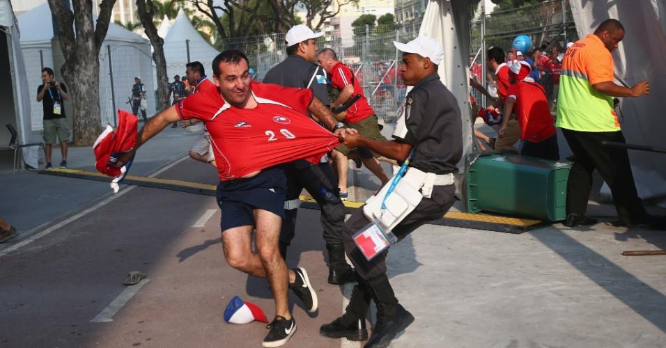Policial tenta conter torcedor chileno durante invasão ao centro de imprensa do Maracanã