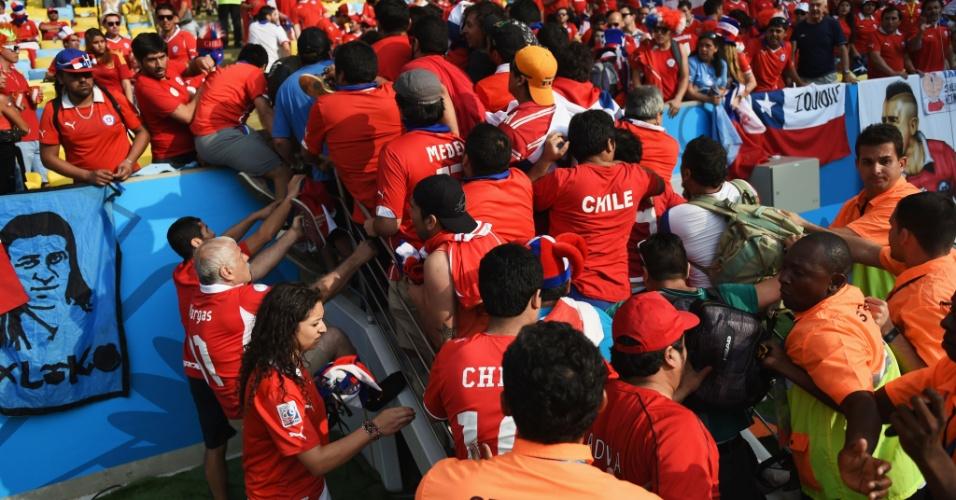 Seguranças tentar impedir que torcedores chilenos invadam o gramado do Maracanã antes do jogo contra a Espanha