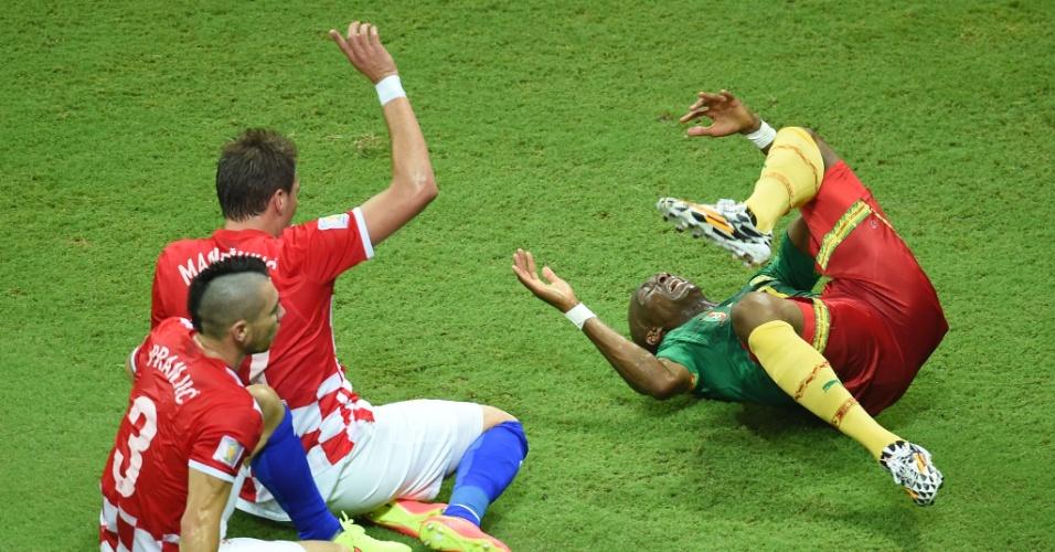 Stephane Mbia, de Camarões, e Danijel Pranjic e Mandzukic, da Croácia, ficam caídos no gramado após dividida