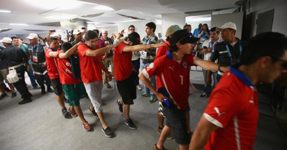 Torcedores chilenos são escoltados pela polícia para fora do Maracanã após tentativa de invasão pelo centro de imprensa