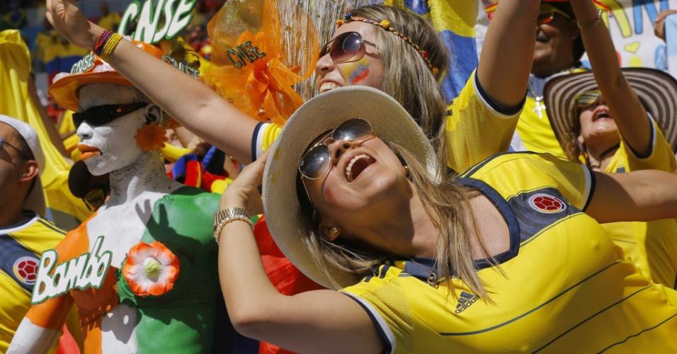 19.jun.2014 - Bela dupla de torcedoras colombianas faz a festa ao lado de torcedor da Costa do Marfim