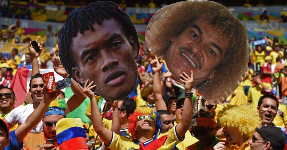 19.jun.2014 - Encontro de gerações e vastas cabeleiras na arquibancada do Mané Garrincha: torcedor colombiano exibe Cuadrado e Valderrama gigantes