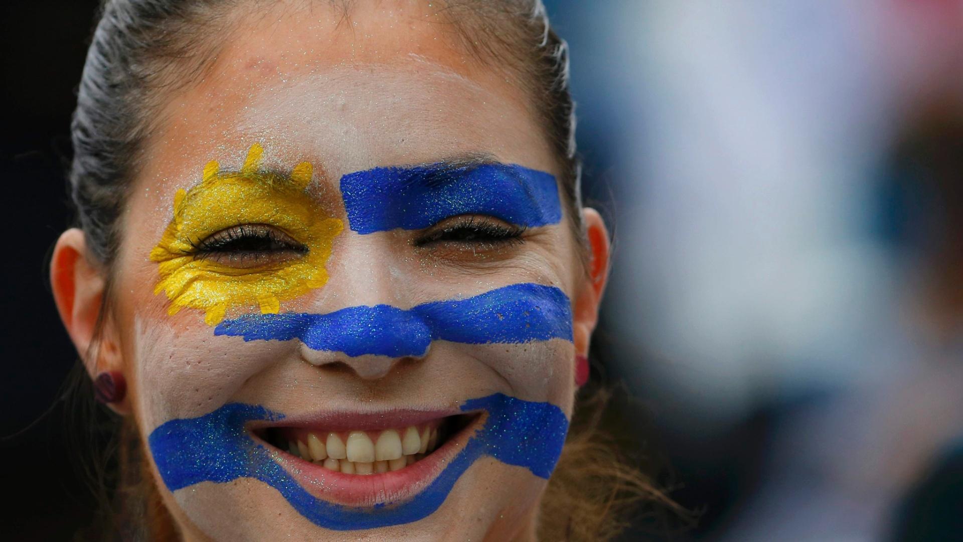 19.jun.2014 - Torcedora pintada com a bandeira uruguaia antes do jogo contra a Inglaterra no Itaquerão