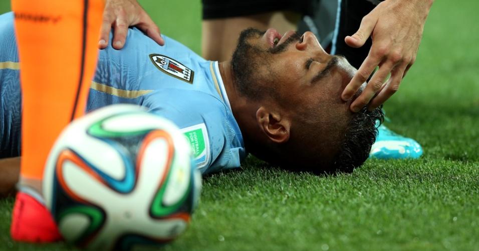 19.jun.2014 - Álvaro Pereira fica caído no gramado para receber atendimento após sofrer uma joelhada contra a Inglaterra