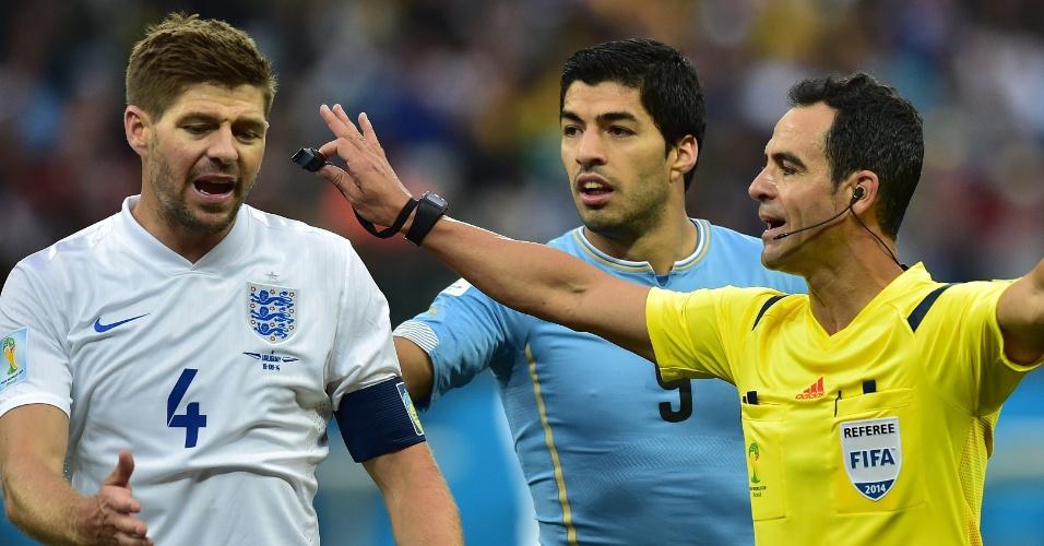 19.jun.2014 - Companheiros de Liverpool, inglês Gerrard e uruguaio Suárez conversam com o árbitro durante o jogo no Itaquerão