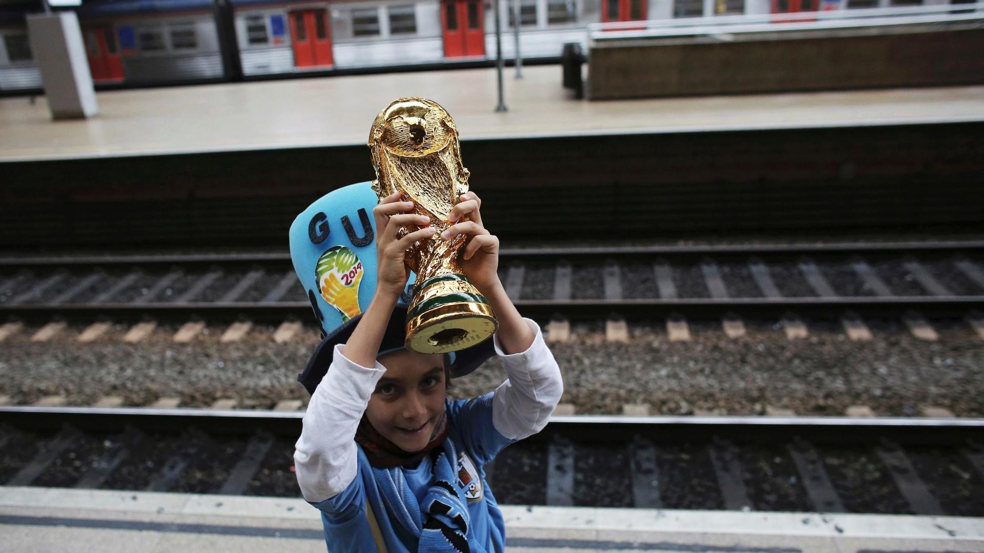 19.jun.2014 - Criança torcedora do Uruguai levanta a taça da Copa do Mundo na estação da Luz, aguardando trem com destino ao Itaquerão, na zona leste de São Paulo