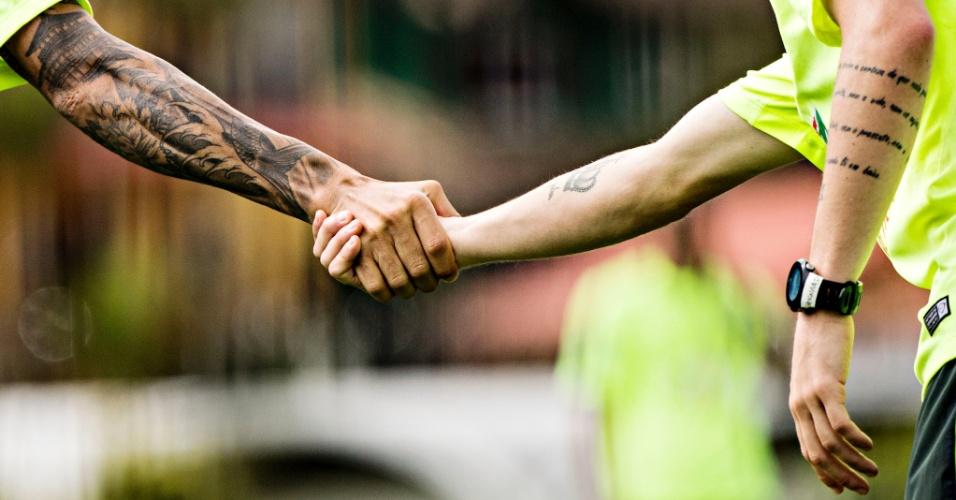 Daniel Alves (esq) e Bernard se cumprimentam e exibem suas tatuagens