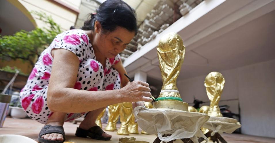 Em Hanói, capital do Vietnam, réplicas de gesso da taça da Copa do Mundo são vendidas por aproximadamente 8 reais