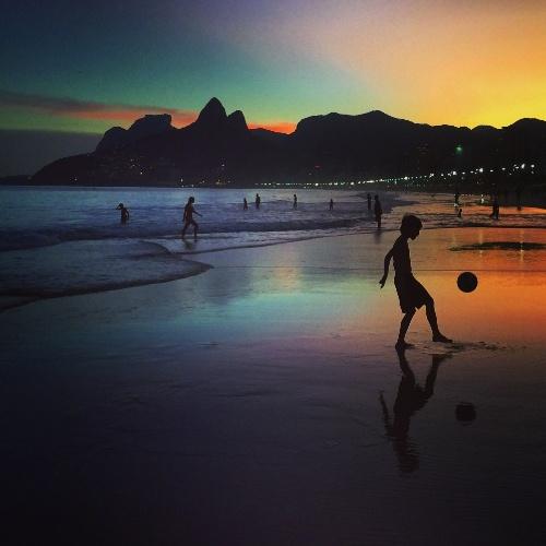 Garoto joga bola no por do sol na praia no Rio de Janeiro na semana da abertura da Copa do Mundo no Brasil