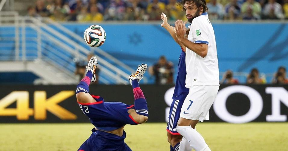Grego Georgios Samaras se protege enquanto o japonês Atsuto Uchida vai de cara no gramado