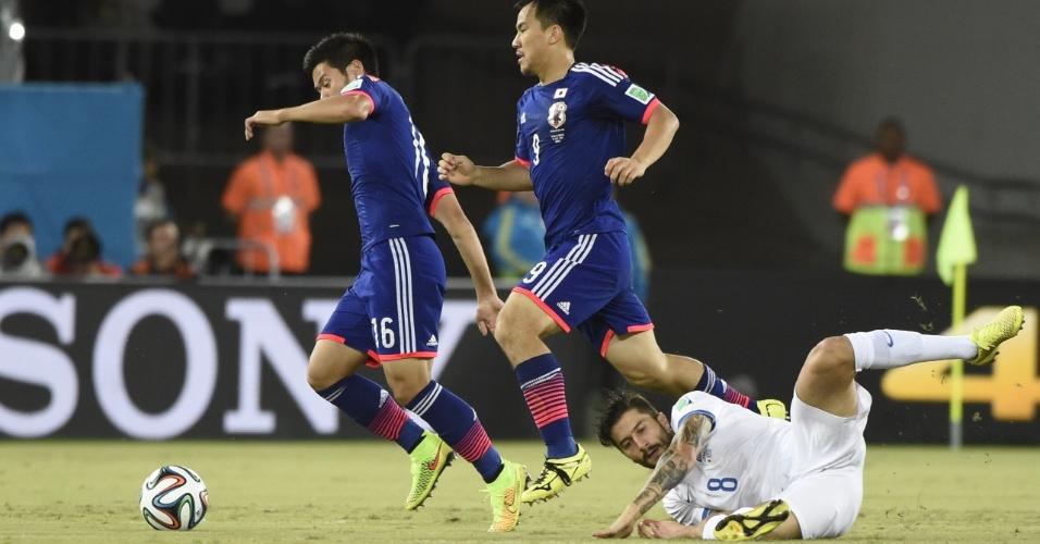 Grego Panagiotis Kone fica caído no gramado enquanto Hotaru Yamaguchi (16) dá sequência a jogada para o Japão