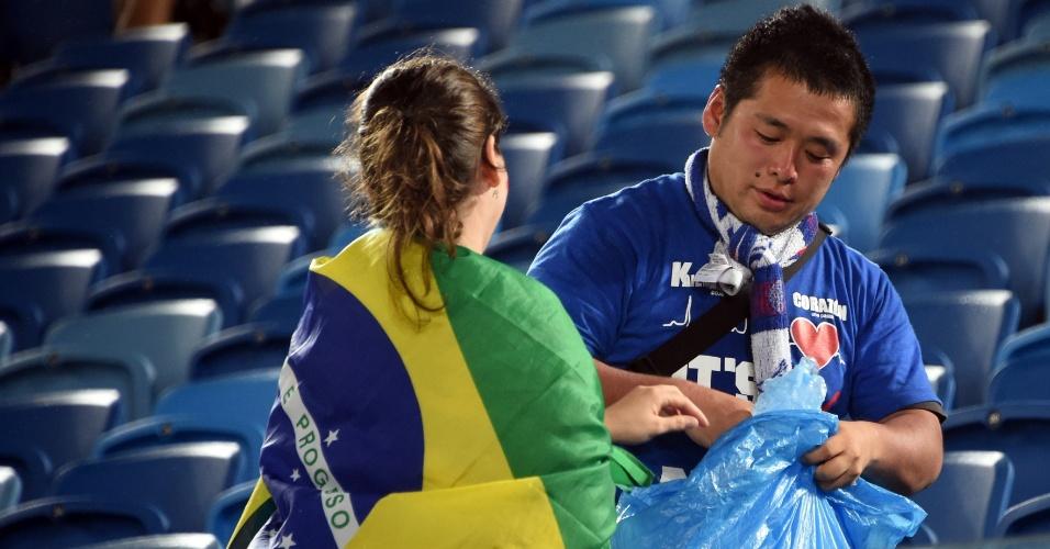 Japonês é ajudado por torcedora brasileira a recolher o lixo que ficou na Arena das Dunas, após jogo entre Japão e Grécia