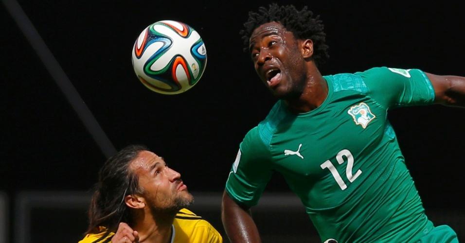 Jogador da Costa do Marfim Wilfried Bony vai às alturas para ganhar a bola de Mario Yepes na partida entre Costa do Marfim e Colômbia