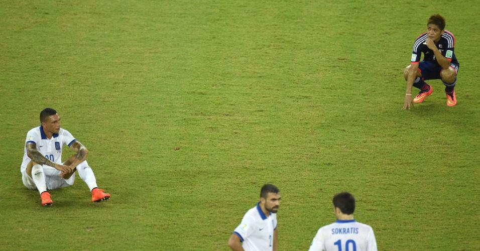 Jogadores das seleções da Grécia e do Japão ficam parados no gramado após o apito final