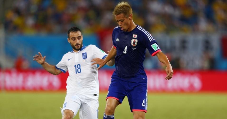 Keisuke Honda, um dos destaques da seleção japonesa, protege a bola de Giannis Fetfatzidis