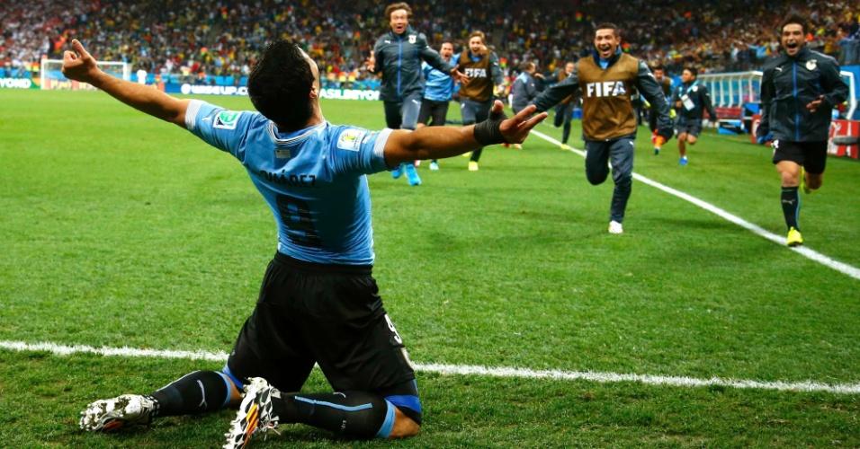 19.jun.2014 - Luis Suárez abre os braços e aguarda companheiros uruguaios para comemorar o segundo gol contra a Inglaterra