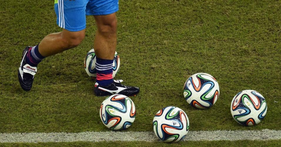 Membro da seleção japonesa recolhe as bolas antes do início do jogo entre Japão e Grécia