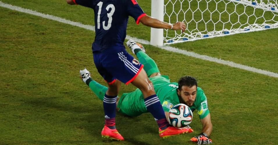 Orestis Karnezis, goleiro da Grécia, briga pela bola com o japonês Yoshito Okubo