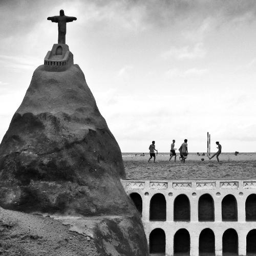 Pelada na praia de Copacabana vista atrás de uma escultura de areia do Corcovado e dos Arcos da Lapa
