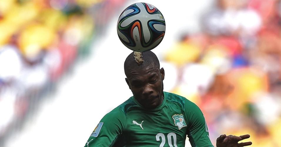 Serey Die parece equilibrar a bola na cabeça durante jogo da Costa do Marfim contra a Colômbia, em Brasília