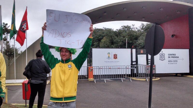 """Torcedor brasileira aguarda chegada da delegação espanhola a Curitiba com um cartaz provocativo: """"Eu já sabia! Adeus Tiki-taka"""""""