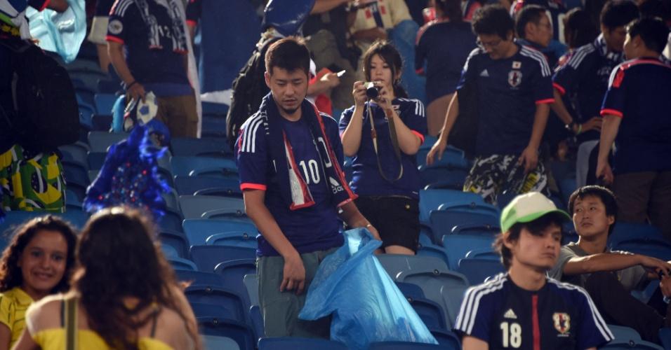 Torcedor japonês usa saco de lixo para limpar parte da Arena das Dunas após jogo contra a Grécia