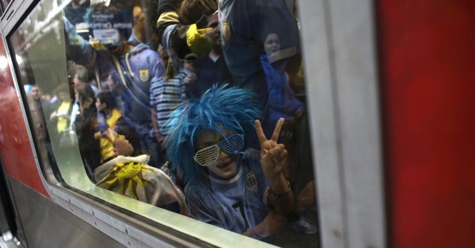 19.jun.2014 - Torcedor uruguaio faz sinal de vitória no trem com destino ao Itaquerão