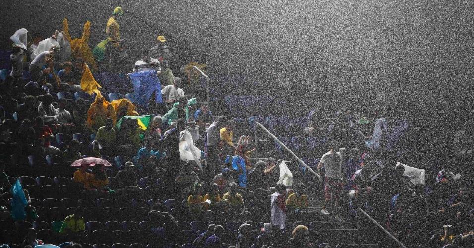 Torcida se protege da chuva que cai na Arena das Dunas