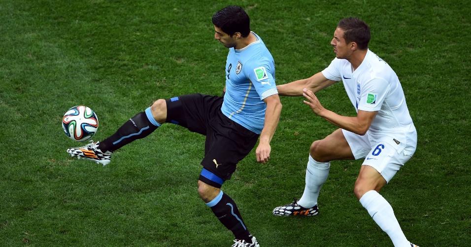 19.jun.2014 - Uruguaio Luis Suárez domina a bola marcado de perto pelo inglês Jagielka, no início da partida no Itaquerão