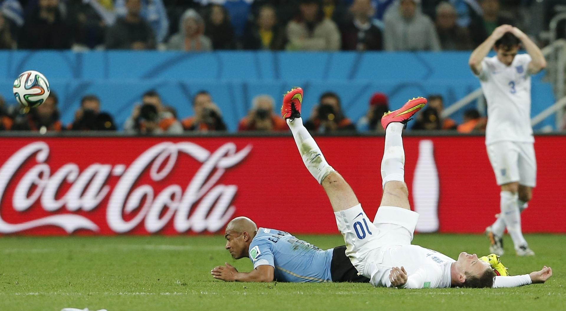 19.jun.2014 - Wayne Rooney fica de pernas para o ar após dividir a bola com o uruguaio Arévalo no Itaquerão