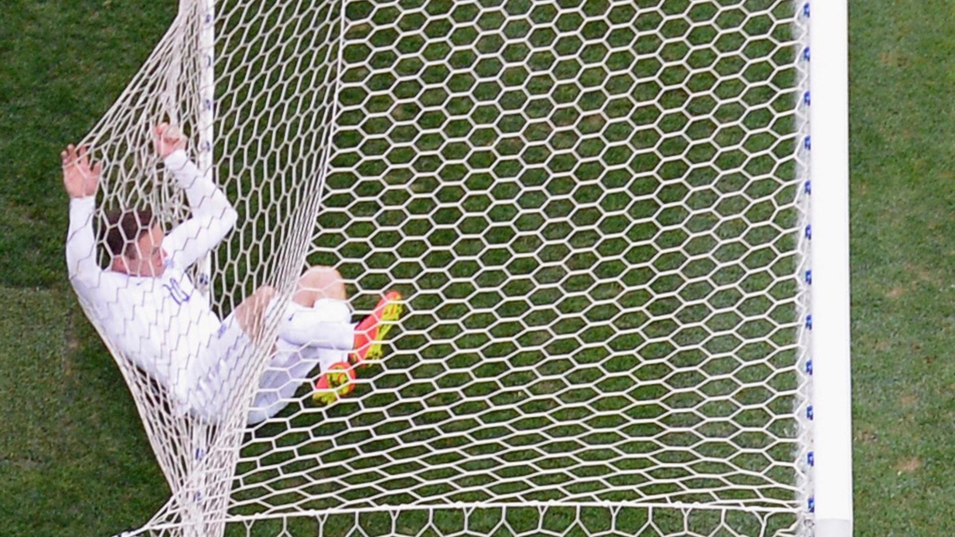 19.jun.2014 - Wayne Rooney fica preso na rede do gol após acertar a trave uruguaia no primeiro tempo da partida